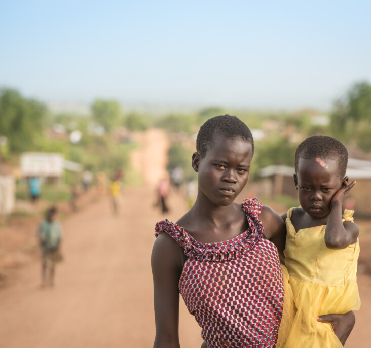 """Annet holds her little sister, Gladys. They faced danger from rebels on the long road from South Sudan to Bidi Bidi. """"They wanted me to untie Gladys from my back and leave her there,"""" Annet remembers. """"I refused. I said, 'If it means dying, we shall all die here.' They beat me but they let us go."""" Photo by Philip Laubner/CRS."""