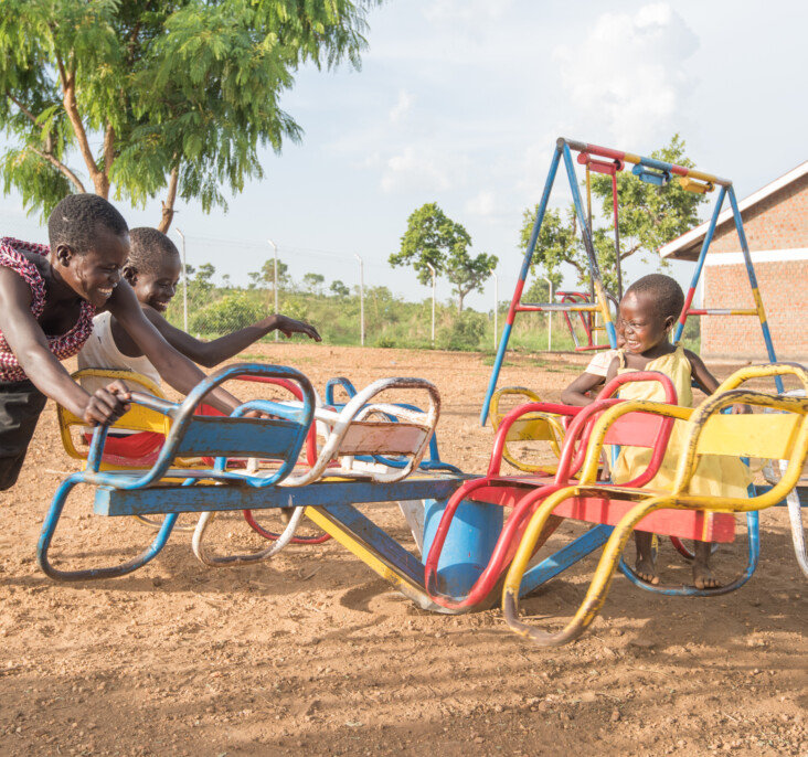 Annet Konga and her family enjoy a playground at the local child-friendly space. These spaces are part of CRS programming and provide a place where children who are dealing with trauma and interrupted educations can learn and heal through play. Photo by Philip Laubner/CRS.