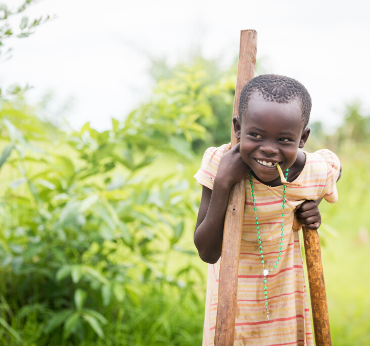 Irene, 8, wields a tool of her own to help Annet collect mud for their new shelter. Photo by Philip Laubner/CRS.
