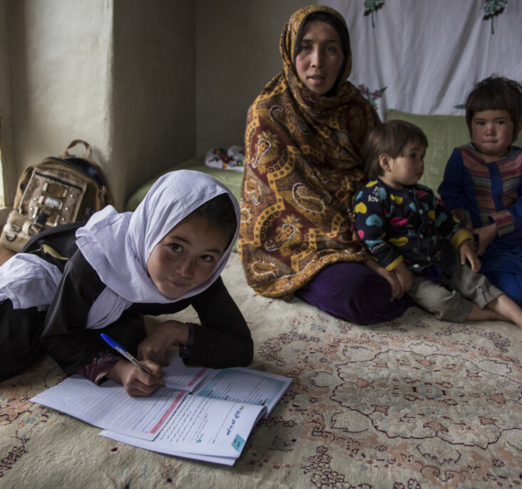 Morzal, 10, does homework surrounded by her family. She is enrolled at a CRS primary school in her remote Afghan village. Morzal wants to study to become a teacher herself one day. Photo by Stefanie Glinski for CRS