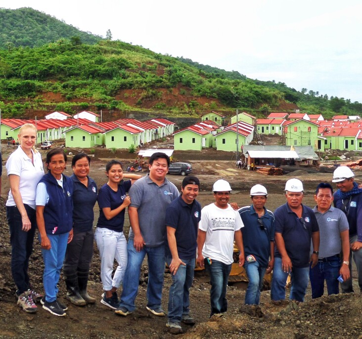 Anibong construction workers gather in front of the nearly complete development, which will house more than 900 families. Photo by CRS Staff.