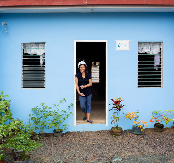 Girlita Ascalona, 37, stands proudly in front of her new home in the Anibong resettlement community. Her previous home was destroyed by Typhoon Haiyan in 2013. CRS is helping her to navigate the complicated process of home ownership. Photo by Jennifer Hardy/CRS.