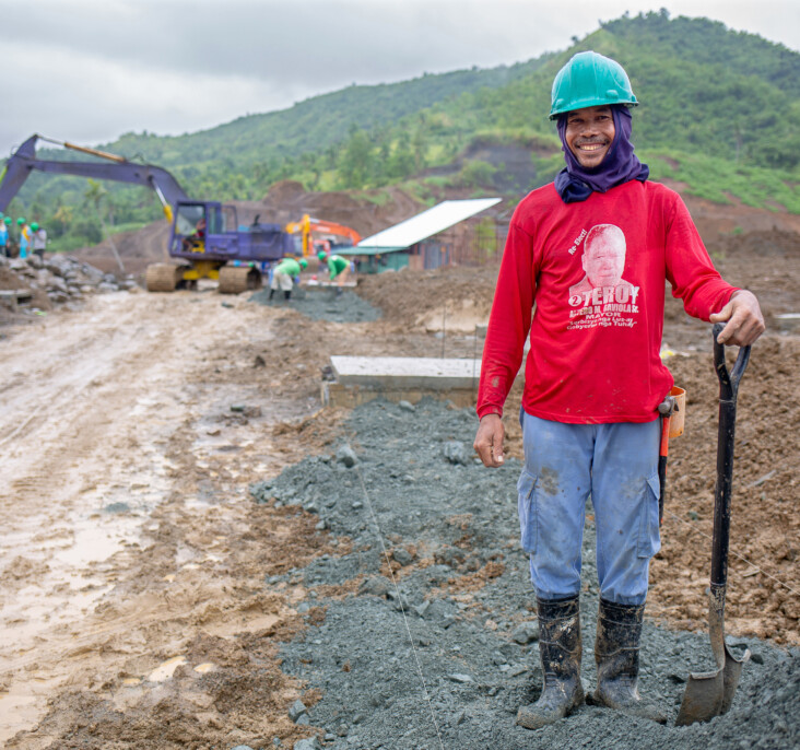 A construction worker stands in the Anibong resettlement site. He is one of many working to provide the new development critical infrastructure like roads and drainage. Photo by Jennifer Hardy/CRS.