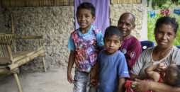 """Louis Gama sits in front of his house in Saelai village in Timor Leste with his wife, Rosa Gama (beneficiary), 40 and his three children: Evangelina Gama, 6 months, Helio Gama, 5 and Aldo Gama, 7. Rosa has been part of the TOMAK CRS program for 6 months. They have lived in this village their entire lives. The family are farmers and tend to their crops daily. They grow maize, beans, sweet potato, vegetables and rice. They sell their vegetables at the local market or trade them for items like salt and oil for cooking. Before participating in the CRS nutrition groups, the mother only fed the baby porridge, but now she knows to mix in vegetables and other foods with protein like eggs that she knows provide vitamins and energy. She has also learned that if the baby is sick, she should continue to breastfeed. """"I didn't know what food my children needed."""" The family also learned that visiting the health clinics for regular checkups is important. """"I have seen improvement in their health because they now weigh more."""" When Aldo's grandfather passed away last year, he was very sad and did not want to go to school anymore so they kept him at home, but he is signed up for next year. Background Timor-Leste has the highest rate of child malnutrition in Asia with almost half of children under five stunted (low height for age). Research shows that rates of exclusive breastfeeding vary widely across the country (28-75%) and there is a lack of dietary diversity with only 13% of children under two years consuming a minimum acceptable diet. On a national level, widespread poor growth is attributed to limited availability of nutritional foods and high child illness burden. Previous research conducted in two (upland and lowland) populations in rural Timor-Leste indicates growth faltering in early development. In Timor-Leste, subsistence agriculture is the main livelihood strategy for the majority of the rural population. Subsistence in Timor-Leste is predominantly plant-based, with staple"""