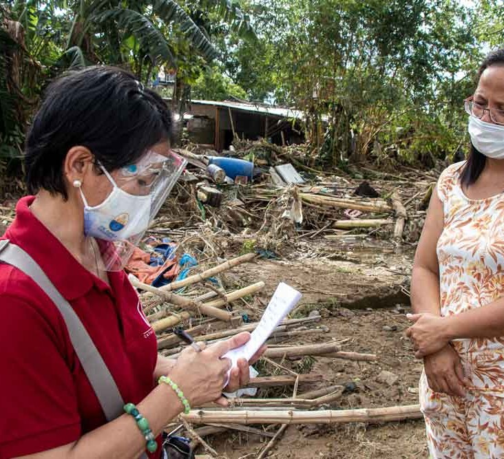 A CRS staff member speaks to a resident of Barangay Burgos.